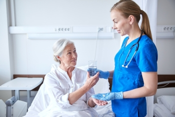 medicine age health care and people concept  nurse giving medication and glass of water to senior woman at hospital ward