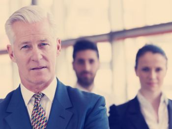 portrait of senior businessman as leader at modern bright office business team people group in background