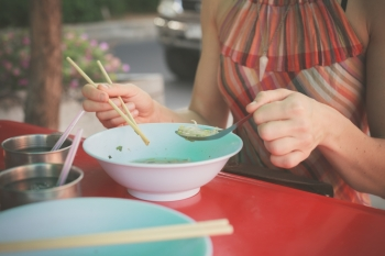 A woman is sitting at a table in the street and is eating noodles