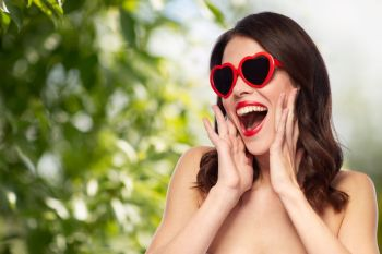 valentines day beauty and people concept  happy smiling young woman with red lipstick and heart shaped sunglasses over green natural background wom