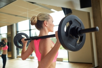 fitness sport powerlifting and people concept  sporty woman exercising with barbell in gym