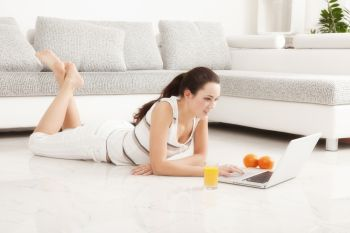 Beautiful Young Woman Surfing the Internet Online on Laptop Orange Juice Lying on the Floor in Living Room