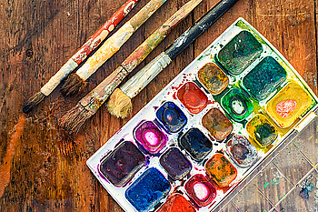 Brush and paint Set of watercolors and different brushes for painting on wood vintage palette