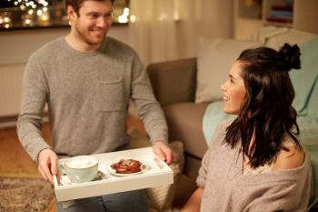 leisure hygge and people concept  happy couple with food on tray at home happy couple with food on tray at home