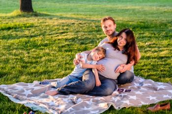 Happy pregnant family of three expecting new baby Father and mother with little boy hugging outdoors