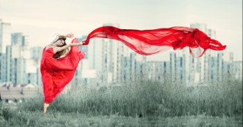 The ballerina is in a beautiful pose and is holding fabric fluttering in the wind at the background of the city