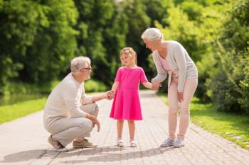 family generation and people concept  happy smiling grandmother grandfather and little granddaughter at park senior grandparents and granddaughter