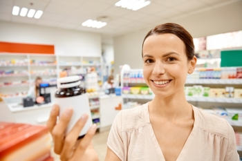 medicine pharmaceutics health care and customer concept  happy female customer with drug jar at pharmacy