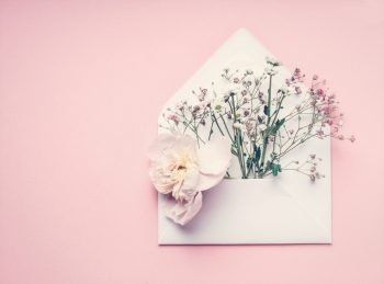 Opened envelop with flowers arrangement on pastel pink background top view copy space Creative greeting Invitation and holiday concept