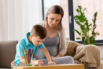 family education and pregnancy concept  happy pregnant mother and little son with workbook writing or drawing at home pregnant mother and son with