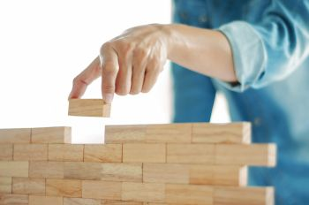 Woman in jeans shirt holding blocks wood game jenga Building concept