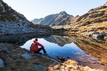 Male hiker takes a rest sitting next a mountain lake Autumn sunny day West italian Alps Oropa Piemonte Italy Europe