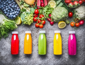 Healthy red orange green yellow and pink Smoothies and juices in Bottles on grey concrete background with fresh organic vegetables  fruits and be