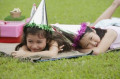 Two girls wearing party hats lying on picnic blanket  resting