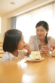 Mid adult woman and her daughter eating a cake