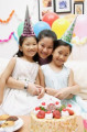 Mother with two girls celebrating a birthday  smiling at camera