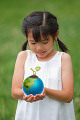 Front view of a girl holding plant sprouting from globe