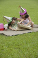 Two girls wearing party hats sitting on picnic blanket  opening a gift