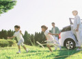 Happy Japanese family with car in a city park