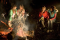 A group of girls chatting around a campfire