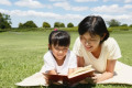 Japanese mother and daughter reading a book in a city park