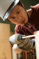 Close-up of a young man drilling a hole in wood