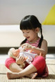 A small girl plays with a doll