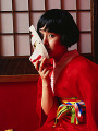 Japanese woman in kimono holding a mask