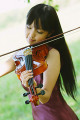 Portrait of an Asian woman playing the violin in a grass field