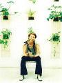 Young woman sitting holding a cup of beverage  potted plants decorated wall background