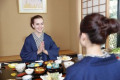 Caucasian woman wearing yukata eating with Japanese friend at traditional ryokan  Tokyo  Japan