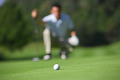 Man Looking at a Golf Ball on a Putting Green