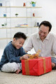 Boy opening gift box  father next to him