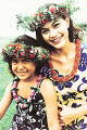 Two sisters wearing traditional hula dancing outfits