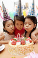 Three girls blowing candles on birthday cake