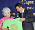 FM Okada news conference October 7  2009  Tokyo  Japan - Japanese Foreign Minister Katsuya Okada  right  is presented with a T-shirt  which bears on its front the logo of Foreign Correspondents rsquo; Club of Japan  prior to his luncheon speech on Wednesday  October 7  2009. Okada  one of the key policymakers of the Yukio Hatoyama administration  talked about the Japan-U.S. relations among other issues.  Photo by Natsuki Sakai/AFLO   3615  -mis-