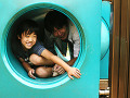 Close-up of a boy sitting in a hollow tube with his father