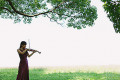 Asian woman playing the violin in a grass field