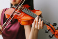 Close up of an Asian woman in a purple dress playing the violin