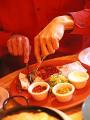 Man slicing Fajita with fork and knife