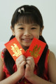 Girl with double happiness red packet  smiling at camera