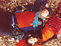 Couple lying on dried leaves covered ground