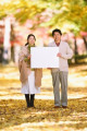 Senior Japanese couple with whiteboard in a city park