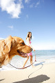 Young woman taking a dog for a walk by the beach