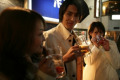 Businessman and two women having beers at night