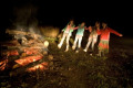 A group of girls dancing around campfire