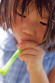 Young Asian girl blowing soap bubbles