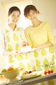 Two Women Holding A Cake In The Kitchen