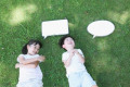 Happy Japanese kids laying with whiteboards in a city park