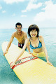 Young man and woman holding surfboard in water